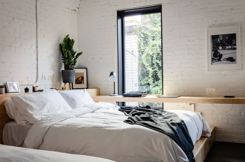 A room at The Annex Hotel in Toronto Canada with white sheets and a large window