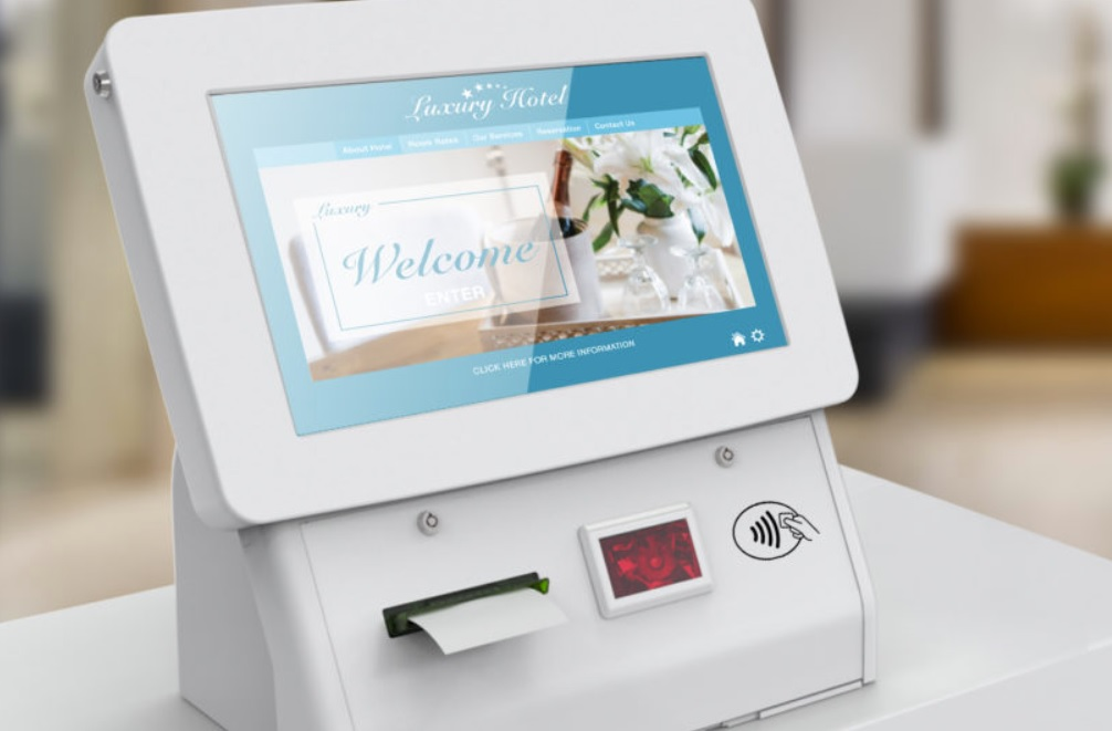 A white computer screen on a table-top kiosk by ImageHolders, displaying a hotel welcome screen and a contactless card payment system