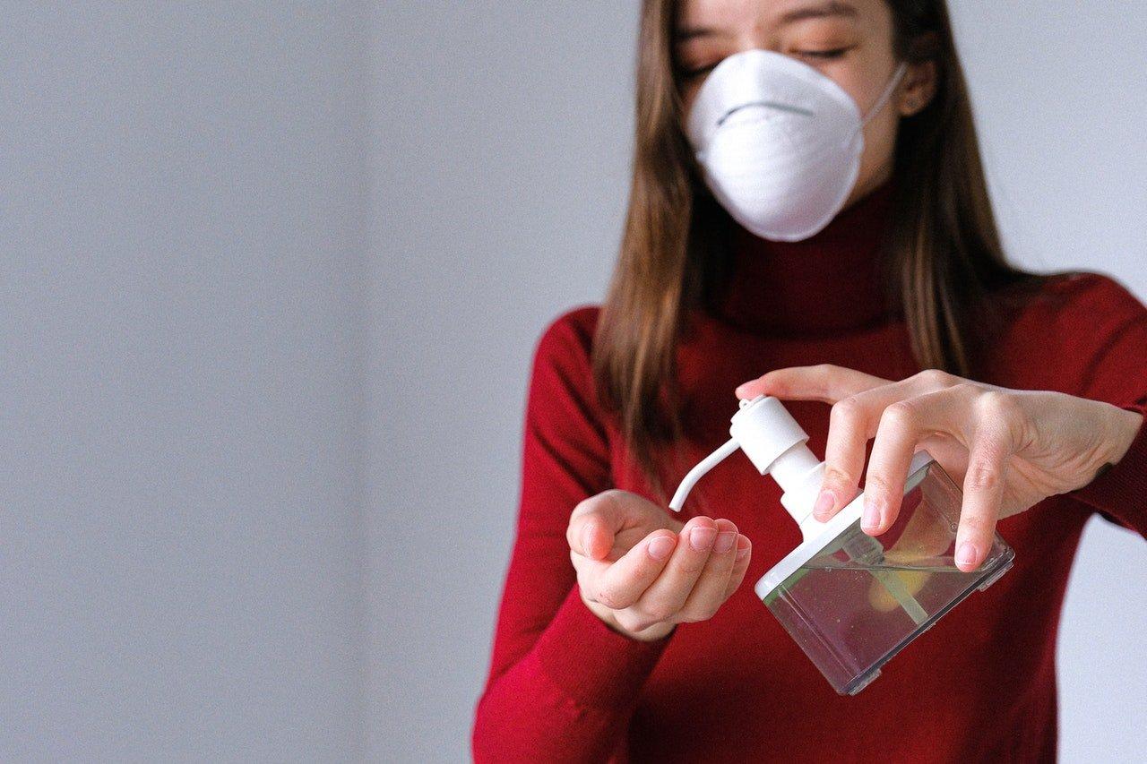 A woman applying hand sanitizer