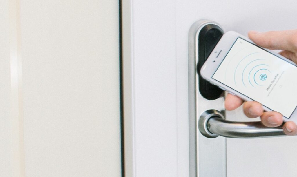 01_Smart home technology works best when it_s all connected. A hand opening a smart lock with a phone