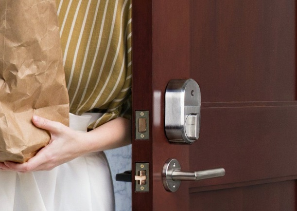 06_Contactless check-in improves your vacation rental security. A woman enters a smart locked door